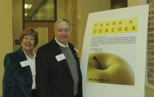 Mrs. Jean and Professor James Bynum next to the poster created by CETL as part of the Thank-a-Teacher Program, with Colonel Stephen Hall's acknowledgment of Professor Bynum's excellence as a teacher, at the Ribbon-Cutting Celebration for the Stephen C. Hall Building (in the main floor lobby).  R.E. Burnett. © 2013. Used with permission.