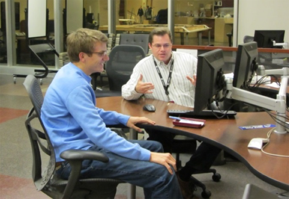 Chad Pearson (Brittain Fellow 2007-2008) works with a library patron at Texas A & M. Photo by Tiana Faultry-Okonkwo.