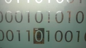 A pane of frosted glass etched with 1s and 0s.