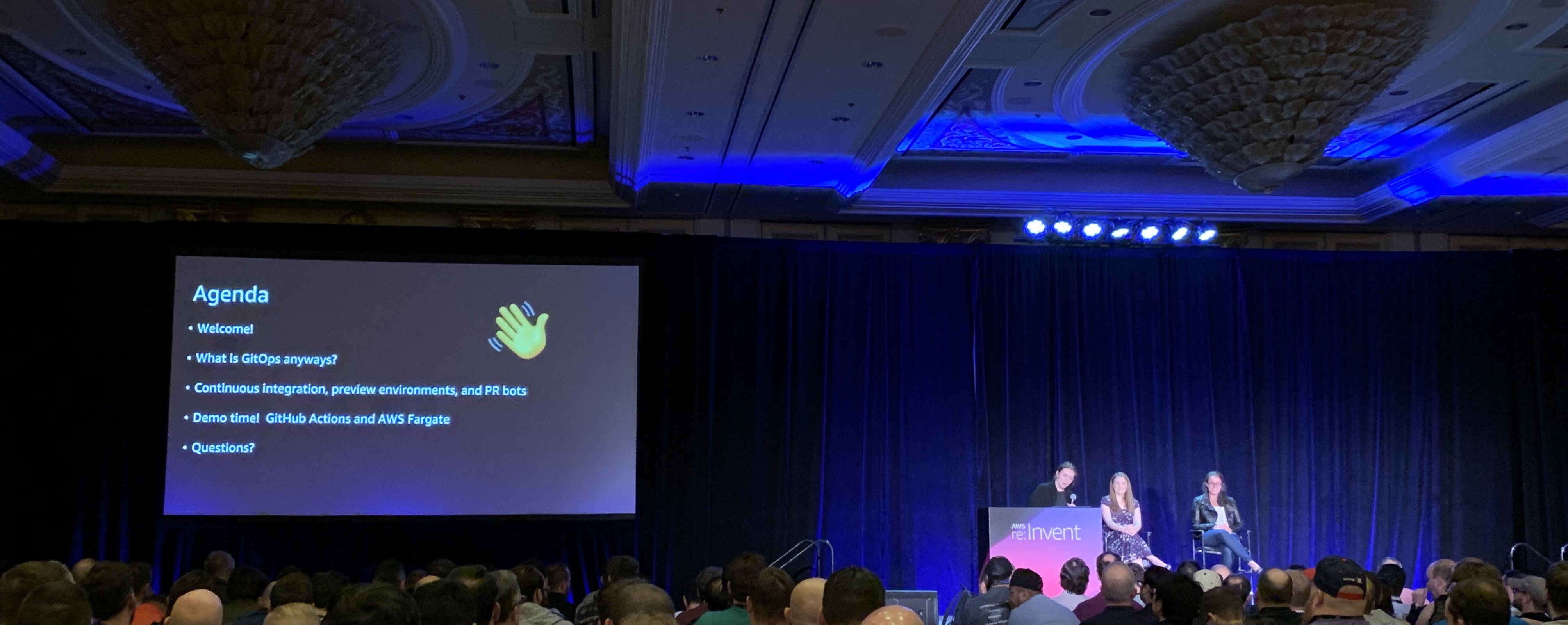 On stage at the Container Power Hour session at the 2018 AWS re:Invent conference. The session agenda is projected on a screen to the left; the session presenters are seated on stage to the right.