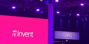 "A sign that reads ""Expo"" is displayed above a door. To the left is a screen projecting text that reads ""AWS re:Invent"""