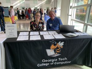 Two people sit behind a table covered in sign-in sheets. The table is covered in a banner for the Georgia Tech College of Computing.