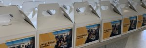 """Rows of lunchboxes are lined up on a table. Each box has a label with the words """"Junior Design Capstone Expo"""" and an image of two people trying virtual reality technology."""