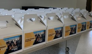 "Rows of lunchboxes are lined up on a table. Each box has a label with the words ""Junior Design Capstone Expo"" and an image of two people trying virtual reality technology."