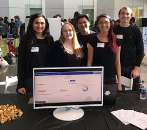 A group of five students stands behind their expo table. The table contains a monitor displaying a visual user interface for an application.