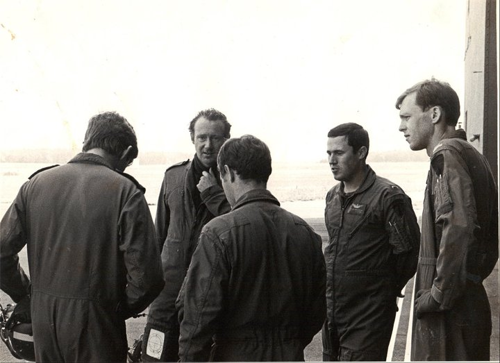 A black and white photo. A group of men in flight suits stand in a circle talking. Bob is pictured on the far right.