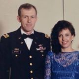 A man in a dress Army uniform stands next to a woman in a blue evening gown.