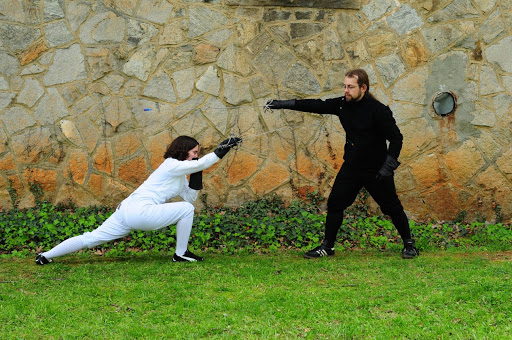 Two people (in fencing gear and with swords in hand) practice fencing techniques in front of a stone wall.