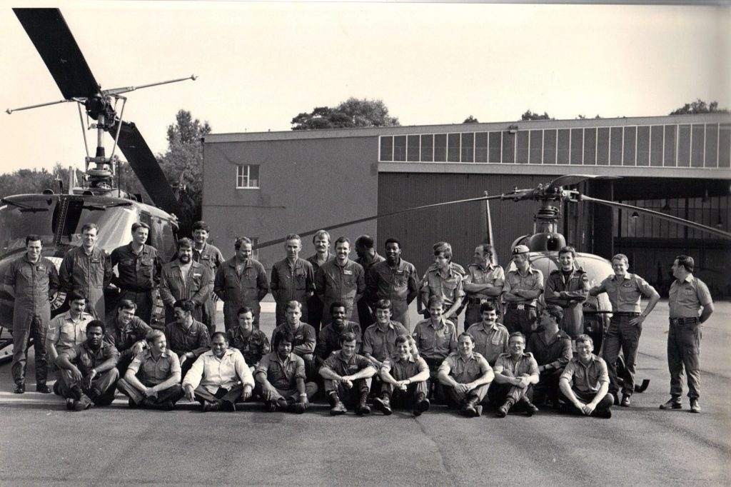 A black and white photo showing a group of army personnel pose in front of two helicopters.