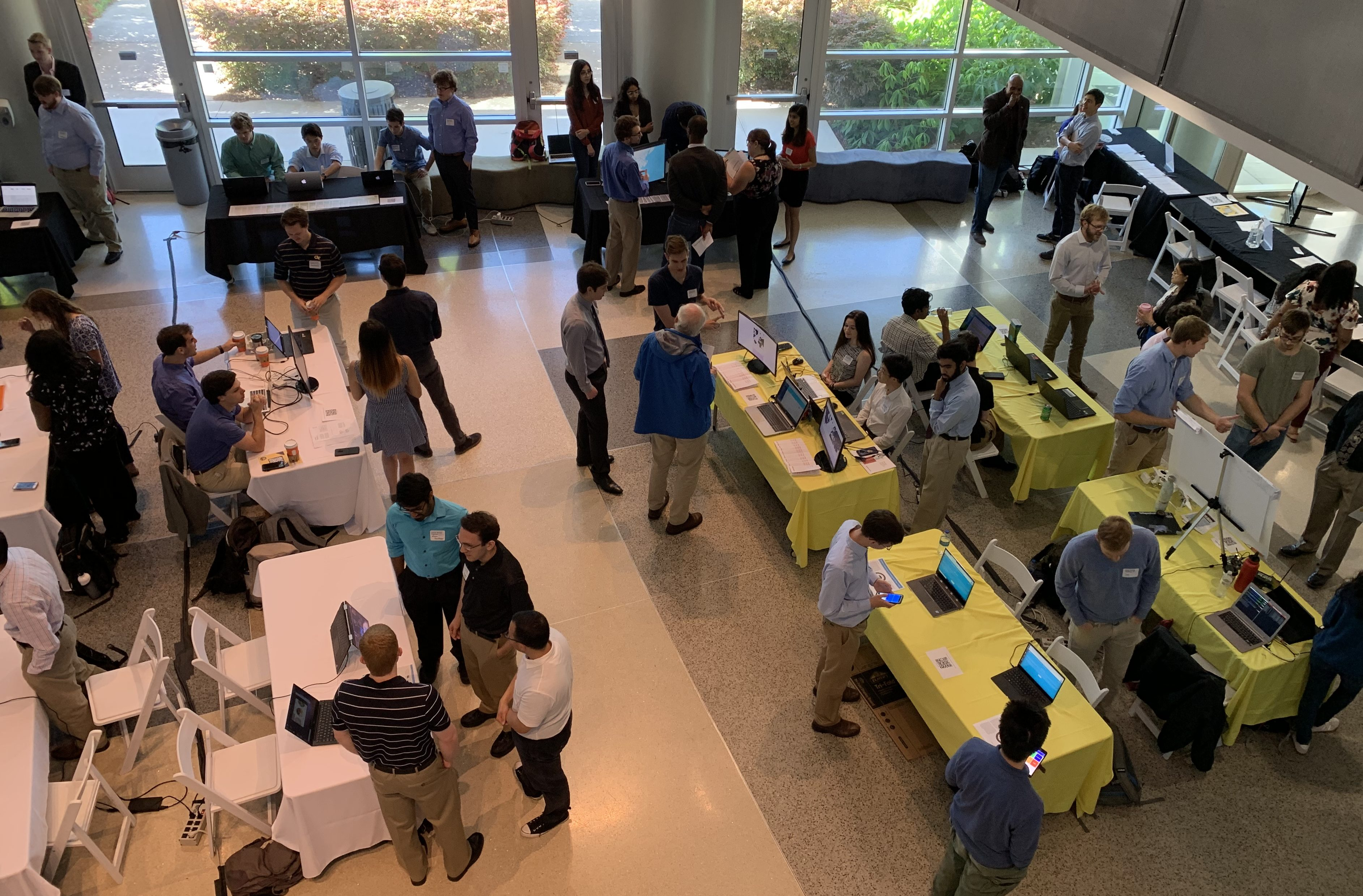 Shot from the second floor of students beginning to set up table displays on the first floor at the Spring 2019 Expo.