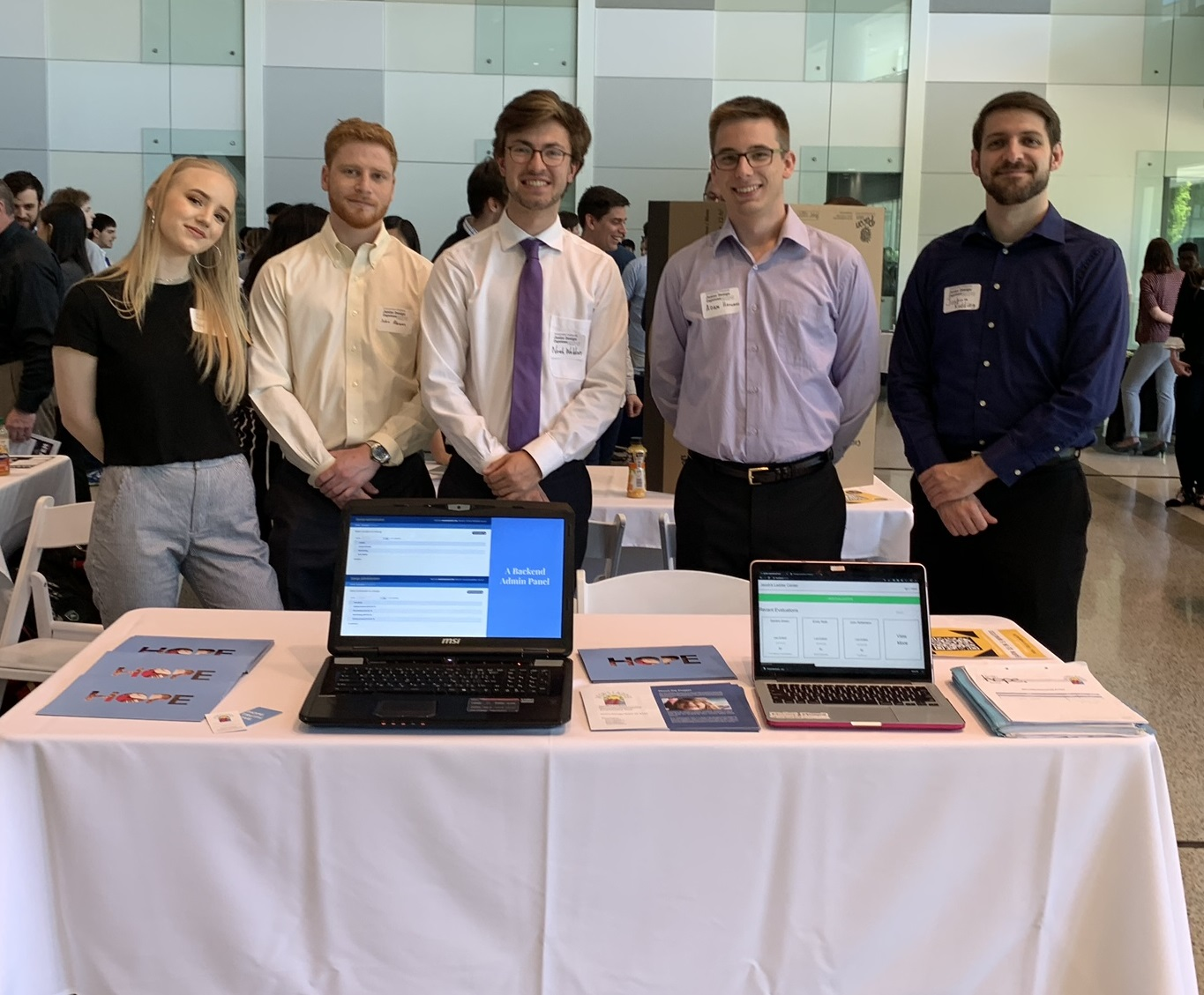 Team 8332 showcases the online evaluation tool they developed for their client, Jacob's Ladder Neurodevelopmental School and Therapy Center. Their table includes two laptops demonstrating the software and handouts describing how the app works.