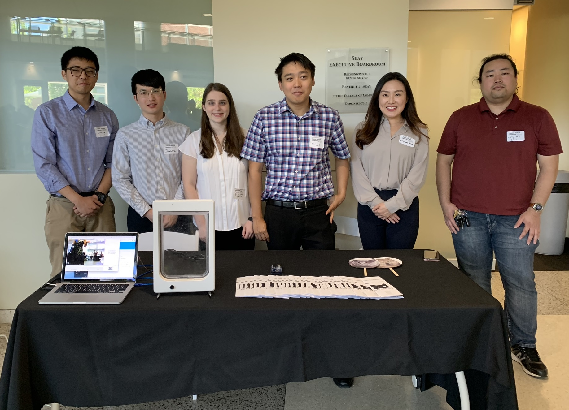 Students stand behind their expo table; the table contains a laptop displaying a software demo, a catdoor used for the demo, brochures for the application, and images of cat, dog, and wolf faces,