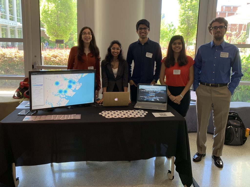 Team 8352 and their project on Visualizing Data from Sea Level Sensors. Table display includes multiple monitors demonstrating the app; a handout explaining the app; and artfully arranged stickers.