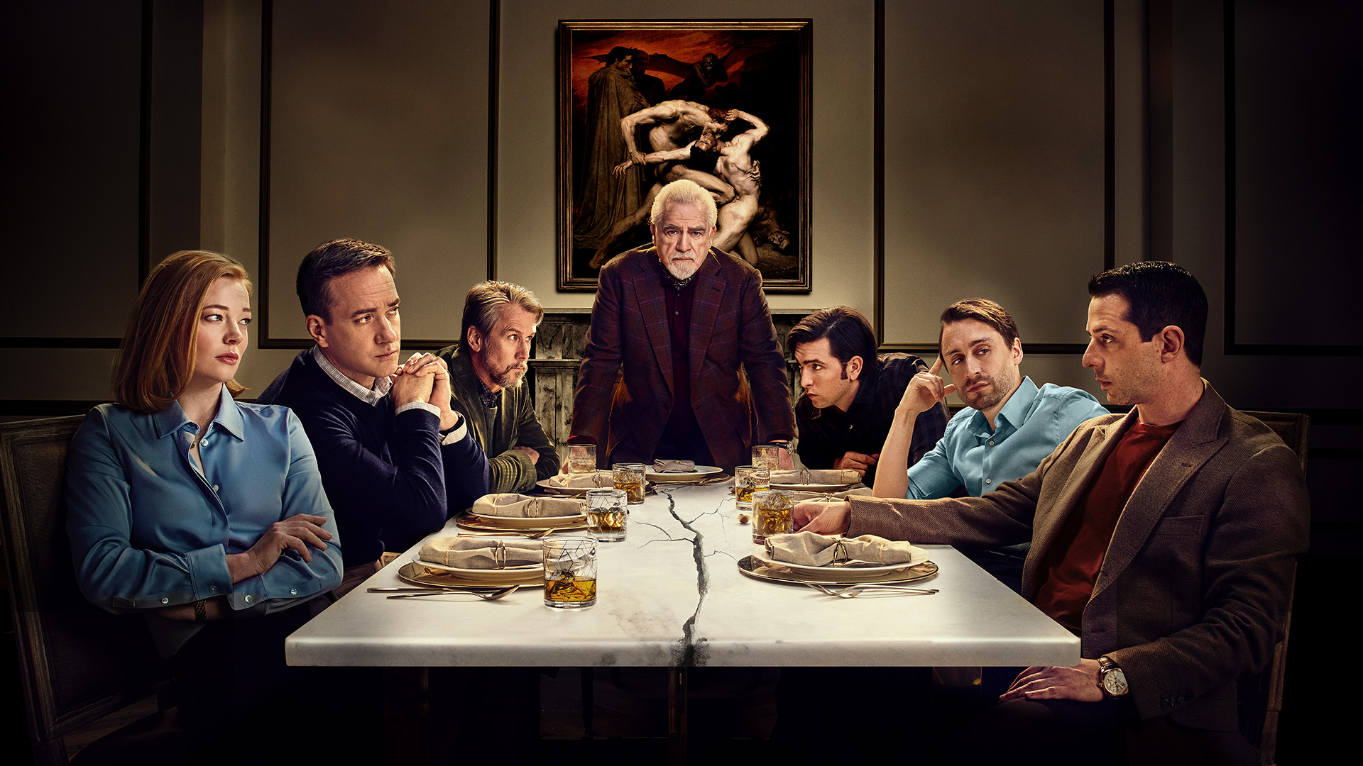 The cast of Succession poses at a dinner table. A crack spreads across the table itself.