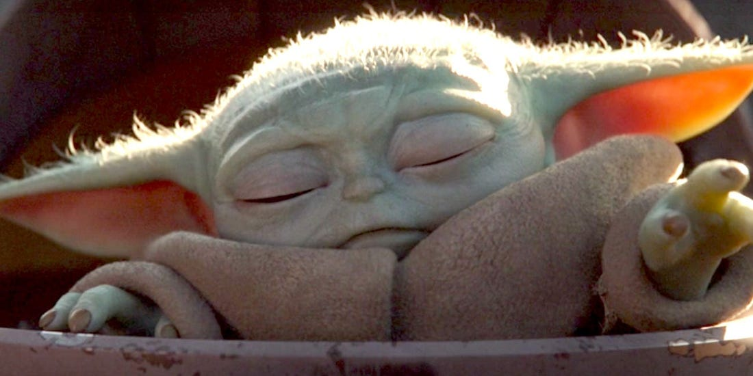 Baby Yoda, with eyes closed, reaches out with his left hand as if to use the Force.