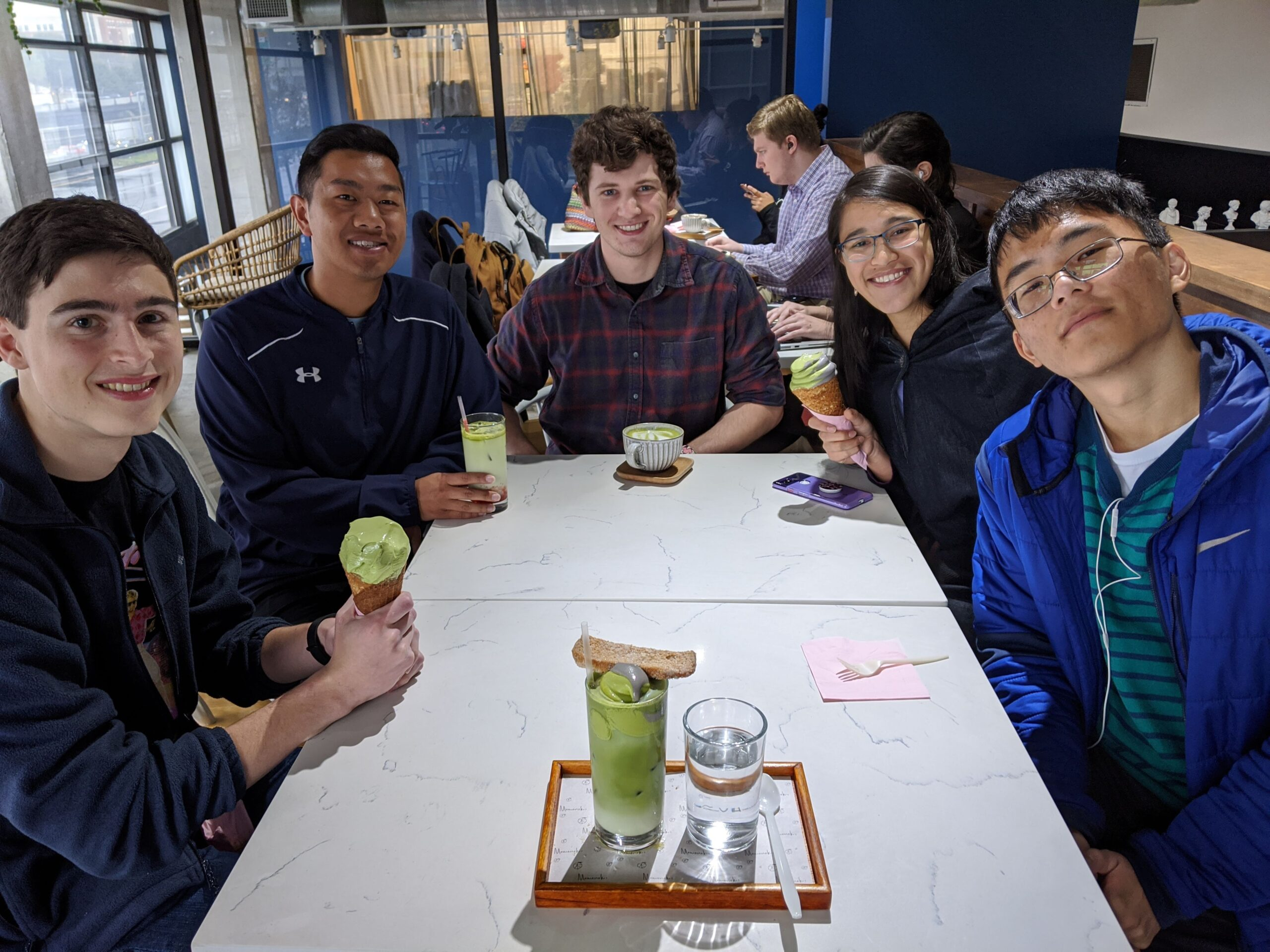 The fab five (L-R: Ryan Power, Alex Yang, Josh Terry, Alayna Panlilio, Jeffrey Zhang) enjoy some ice cream at Momo Cafe. The team members sit at a rectangular table, holding ice cream and smiling at the camera.