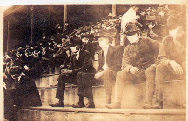 people wearing masks at a football game in 1918