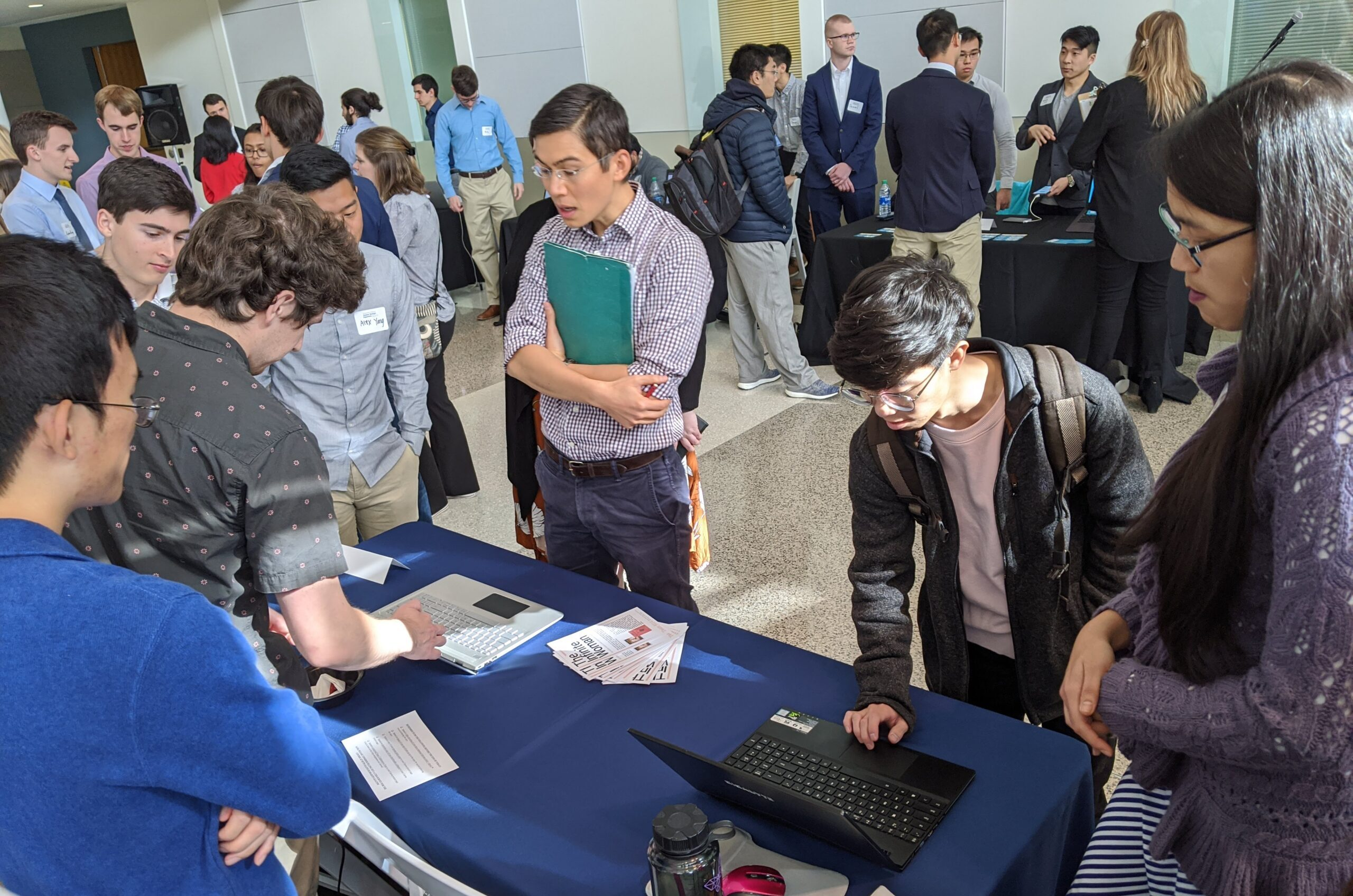 The team presents their project at Georgia Tech's Junior Design Capstone Expo in December 2019. Visitors interact with laptops displaying the project, while team members discuss with them.