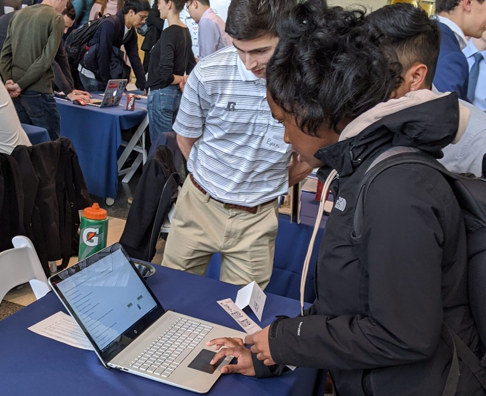 The team presents their project at Georgia Tech's Junior Design Capstone Expo in December 2019. A visitor interacts with a laptop displaying the project, making an erasure poem while team members look on.