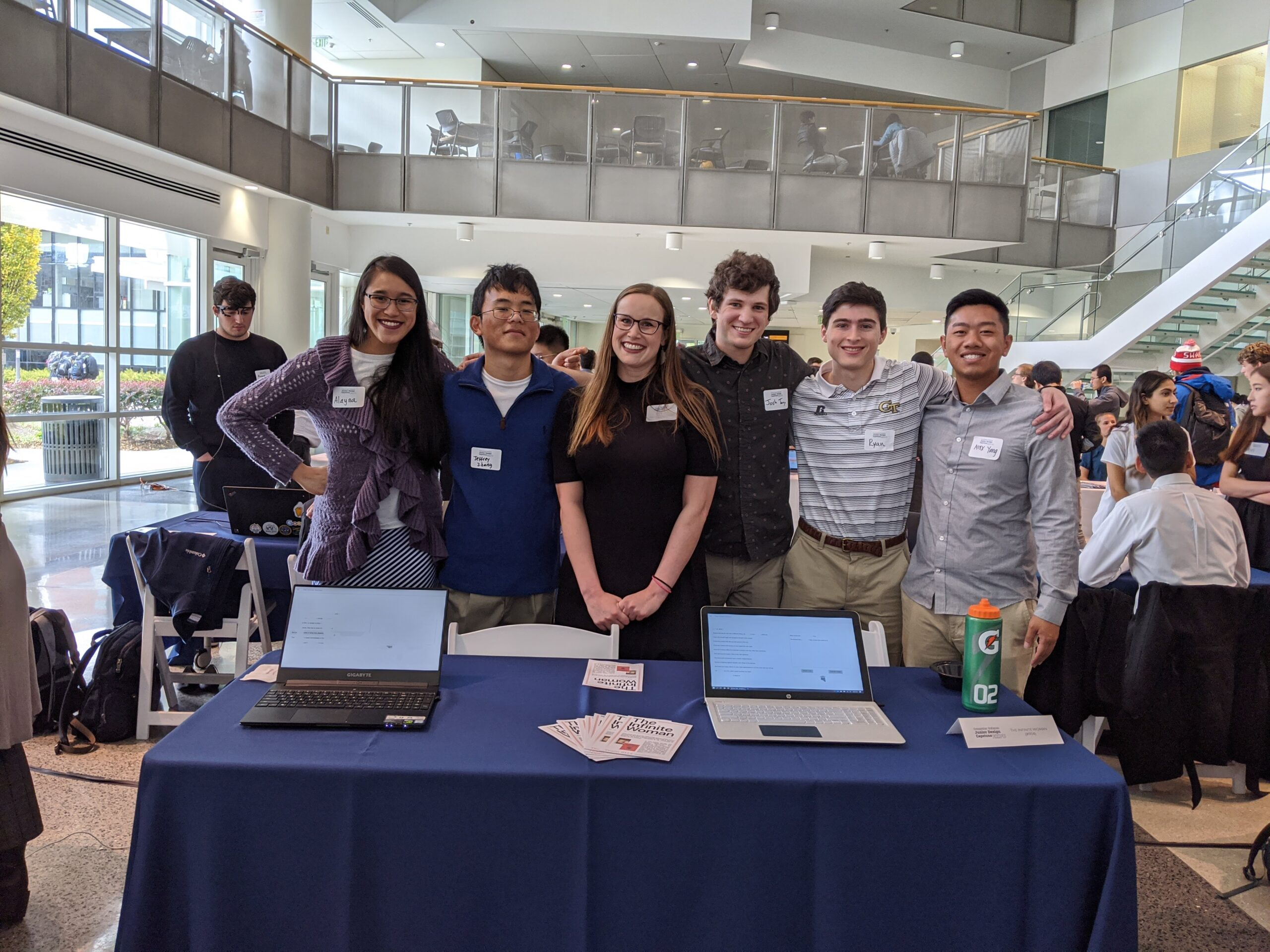 Six smiling people stand behind a table displaying laptops and brochures in a busy atrium.