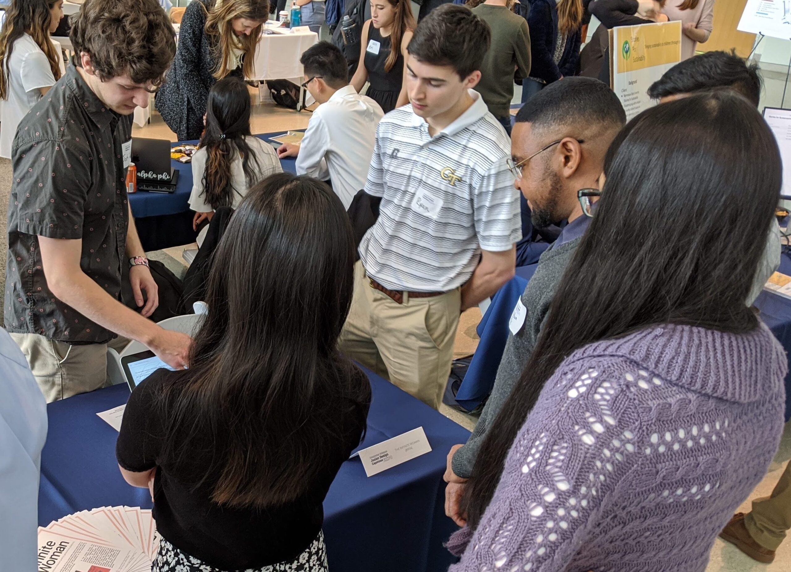 A group of people stand in a circle interacting with a laptop on a table in a busy atrium.