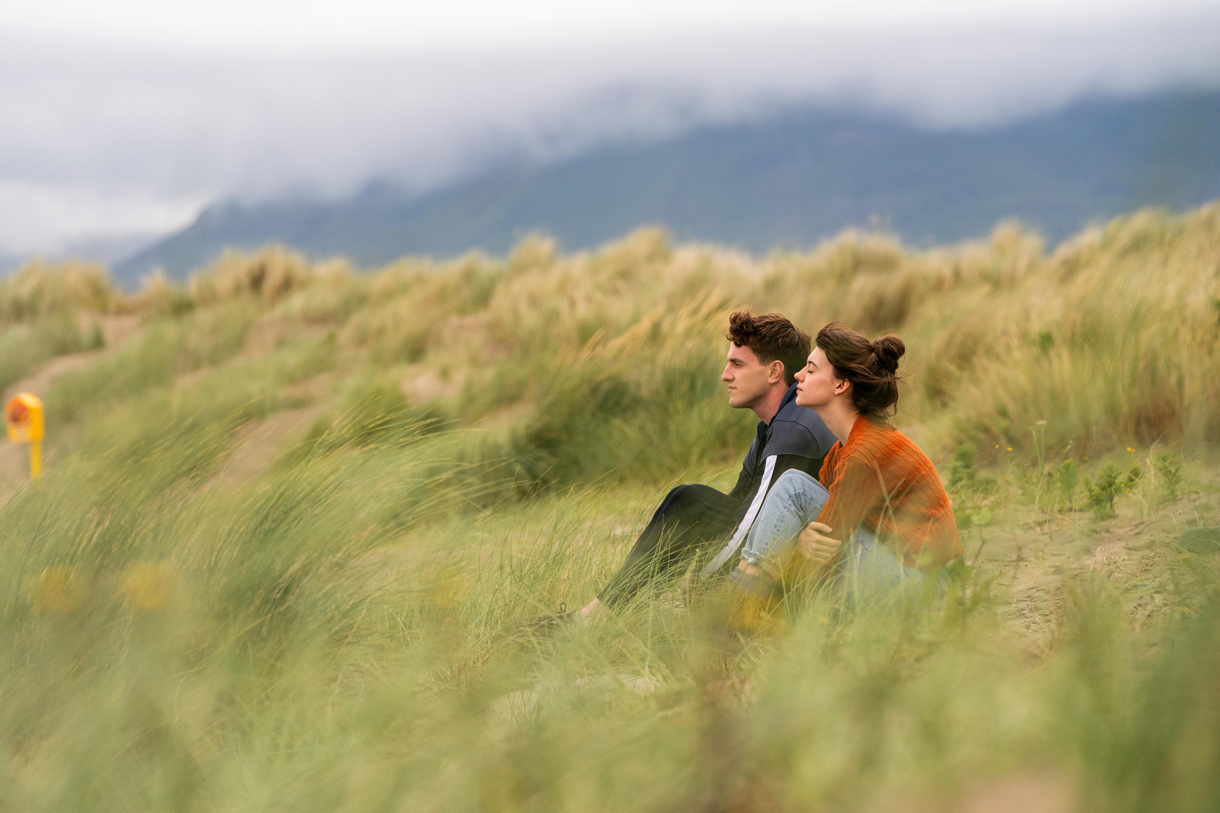 """Actress Daisey Edgar-Jones (as Marianne) and actor Paul Mescal (as Connell) sit together in tall, green grass and face an on-coming wind in this still from the Hulu show """"Normal People."""""""