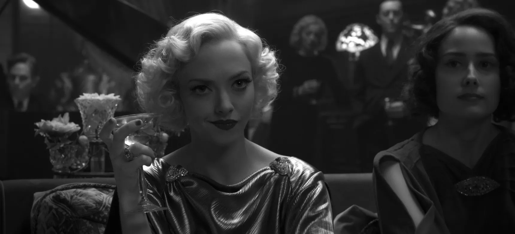 Amanda Seyfried, as Marion Davies in Mank, sits at a party in formal dress. Sheis holding a martini and has a wry smile on her face.