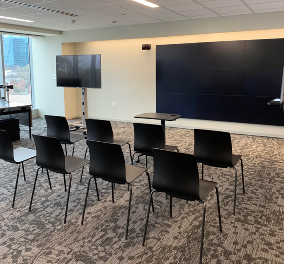 A meeting room with a few chairs and two large displays.